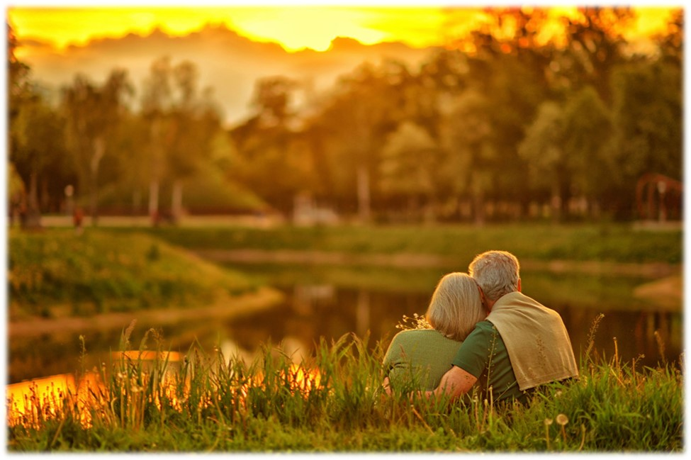 Mature couple sitting by pond